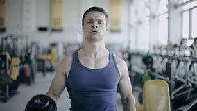 Το άτομο bodybuilder εκτελεί την άσκηση με τους αλτήρες στη γυμναστική Πλήρης πυροβολισμός προσώπου φιλμ μικρού μήκους