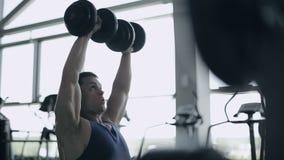 Το άτομο bodybuilder εκτελεί την άσκηση με τους αλτήρες στη γυμναστική Σχεδιάγραμμα του πυροβολισμού προσώπου φιλμ μικρού μήκους