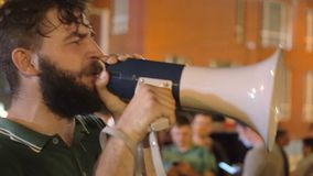 Το άτομο Hipster οδηγεί τη φλογερή ομιλία με megaphone στη συνάθροιση και δίνει την ισχυρή ομιλία φιλμ μικρού μήκους
