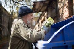 Το άτομο Homeles που ψάχνει τα τρόφιμα ξυλοφορτώνει μέσα μπορεί Στοκ φωτογραφία με δικαίωμα ελεύθερης χρήσης