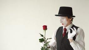 Το άτομο mime με ένα κόκκινο αυξήθηκε σε ένα άσπρο υπόβαθρο Τα δάχτυλα της MIM που τσιμπήθηκαν στο αγκάθι αυξήθηκαν απόθεμα βίντεο