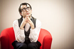 Το άτομο Nerd περιμένει στην κόκκινη πολυθρόνα Στοκ Εικόνα