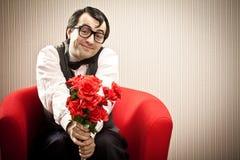 Το άτομο Nerd περιμένει την αγάπη του στην κόκκινη πολυθρόνα με το δώρο λουλουδιών Στοκ φωτογραφίες με δικαίωμα ελεύθερης χρήσης