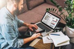 Το άτομο Oung, επιχειρηματίας, freelancer κάθεται στο σπίτι στον καναπέ στο τραπεζάκι σαλονιού, χρησιμοποιεί το smartphone, εργαζ Στοκ Φωτογραφίες