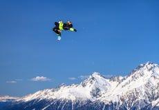Το άτομο snowboarder πετά την ελεύθερη κολύμβηση από ένα άλμα στην αιχμή βουνών Chugush και το υπόβαθρο μπλε ουρανού στο χειμώνα στοκ φωτογραφίες με δικαίωμα ελεύθερης χρήσης