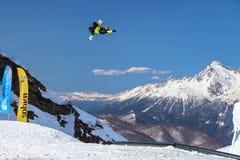 Το άτομο snowboarder πετά την ελεύθερη κολύμβηση από ένα άλμα στην αιχμή βουνών Chugush και το υπόβαθρο μπλε ουρανού στο χειμώνα στοκ φωτογραφία με δικαίωμα ελεύθερης χρήσης