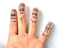 Το δάχτυλο στη δακτυλήθρα που οπλίζεται από τη βελόνα υποβάλλει το φόβο ένα άλλα δάχτυλα Στοκ Εικόνες