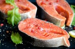 Το άλας πιπεριών μπριζολών σολομών πρασινίζει το μαύρο πιάτο Στοκ Εικόνες