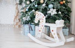 Το άλογο λικνίσματος παιχνιδιών παιδιών ` s είναι ένα άσπρο χριστουγεννιάτικο δέντρο Κοντινό λ Στοκ φωτογραφίες με δικαίωμα ελεύθερης χρήσης