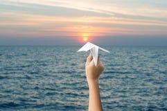 Το έγγραφο αεροπλάνων στα χέρια και το ηλιοβασίλεμα παιδιών, διαβιβάζει στο στόχο Στοκ Εικόνες