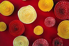 Το έγγραφο κινείται σπειροειδώς κίτρινος και πορτοκαλής σε ένα κόκκινο υπόβαθρο Στοκ φωτογραφίες με δικαίωμα ελεύθερης χρήσης