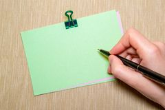 το έγγραφο με το χέρι paperclip και γυναικών κρατώντας μια μάνδρα περίπου που γράφει Αντικείμενα που απομονώνονται σε κίτρινο Στοκ Εικόνες