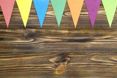 Το έγγραφο σημαιοστολίζει τη γιρλάντα κομμάτων στο ξύλινο υπόβαθρο Στοκ Εικόνες