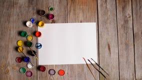 Το έγγραφο, τα watercolors, η βούρτσα χρωμάτων και κάποια τέχνη γεμίζουν στην ξύλινη ετικέττα Στοκ φωτογραφία με δικαίωμα ελεύθερης χρήσης