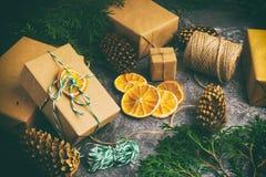 Το έγγραφο τεχνών παρουσιάζει κιβωτίων σκοινιού του FIR δέντρων ξηρά τεμαχισμένα πορτοκαλιά φρούτα σφαιρών κλάδων τα κόκκινα στο  Στοκ Φωτογραφίες