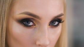 Το έγκαυμα κοιτάζει Το εκφραστικό makeup στα μάτια, πολύ όμορφο κορίτσι κοιτάζει αδιάφορα στο πλαίσιο φιλμ μικρού μήκους
