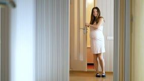 Το έγκυο κορίτσι βγαίνει από την πόρτα και επιδεικνύει το νέο nightie της Πρώτη εγκυμοσύνη Ευτυχές brunette με cub φιλμ μικρού μήκους
