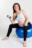 Το έγκυο κορίτσι κάθεται στο fitball με τους αλτήρες Στοκ φωτογραφίες με δικαίωμα ελεύθερης χρήσης