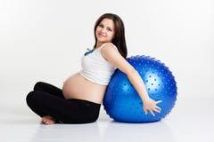 Το έγκυο κορίτσι κρατά fitball κοντά σε την πίσω Στοκ Εικόνες