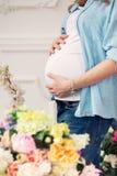 Το έγκυο κορίτσι με τα λουλούδια Στοκ Φωτογραφία