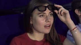 Το έκπληκτο κορίτσι βγάζει τα τρισδιάστατα γυαλιά για να εξετάσει καλύτερα τη στιγμή στον κινηματογράφο απόθεμα βίντεο