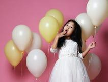 Το έκπληκτο κορίτσι παιδιών με τα μπαλόνια στο φόρεμα πριγκηπισσών με την τιάρα κρατά το μπαλόνι στοκ εικόνες