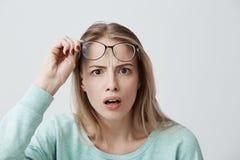 Το έκπληκτο νέο θηλυκό πρότυπο με τη μακριά ξανθή τρίχα, φορά τα γυαλιά και το μπλε μακρύς-sleeved πουκάμισο, εξετάζει με τον τρό στοκ εικόνες