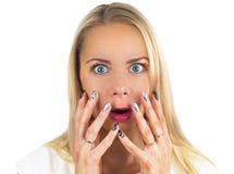 Το έκπληκτο ξανθό κορίτσι με τα μπλε μάτια κραυγάζει και κλείνει το στόμα με τα χέρια της από την έκπληξη παρουσιάζοντας το προϊό Στοκ Εικόνα