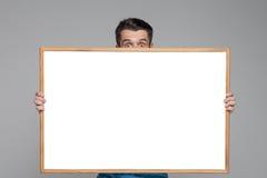 Το έκπληκτο άτομο που παρουσιάζει κενό άσπρο πίνακα διαφημίσεων ή Στοκ φωτογραφίες με δικαίωμα ελεύθερης χρήσης