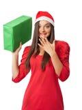 Το έκπληκτο κορίτσι στο καπέλο αρωγών ενός Santa κρατά ένα πράσινο δώρο Στοκ φωτογραφίες με δικαίωμα ελεύθερης χρήσης