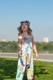 Το έκπληκτο μικρό κορίτσι παίζει με τις φυσαλίδες σαπουνιών Στοκ Εικόνες