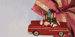 Το έμβλημα Χριστουγέννων με το santa παιχνιδιών σε ένα αναδρομικό αυτοκίνητο με έναν τάρανδο και έναν σωρό παρουσιάζει στην κορυφ στοκ εικόνες