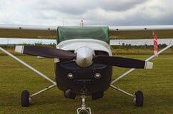 Το ένα αεροπλάνο μηχανών στέκεται στην πράσινη χλόη σε μια νεφελώδη ημέρα Μπροστινή άποψη της πεδιάδας Ένα μικρό ιδιωτικό αεροδρό στοκ φωτογραφία