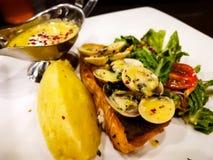 Το ένα κομμάτι του τηγανιού ο σολομός σε ένα άσπρο πιάτο με τα φύλλα μαρουλιού που εξυπηρετήθηκαν με τη σάλτσα ταρτάρου Στοκ Φωτογραφίες