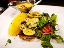Το ένα κομμάτι του τηγανιού ο σολομός σε ένα άσπρο πιάτο με τα φύλλα μαρουλιού που εξυπηρετήθηκαν με τη σάλτσα ταρτάρου Στοκ εικόνα με δικαίωμα ελεύθερης χρήσης