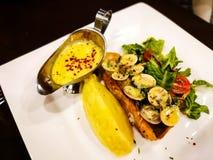 Το ένα κομμάτι του τηγανιού ο σολομός σε ένα άσπρο πιάτο με τα φύλλα μαρουλιού που εξυπηρετήθηκαν με τη σάλτσα ταρτάρου Στοκ Φωτογραφία