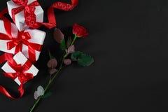 Το ένα σκούρο κόκκινο αυξήθηκαν και το κιβώτιο δώρων με την κόκκινη κορδέλλα στο μαύρο backgrou Στοκ Εικόνες