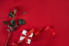 Το ένα σκούρο κόκκινο αυξήθηκε με το κόκκινο κιβώτιο κορδελλών και δώρων στο κόκκινο υπόβαθρο Στοκ Φωτογραφίες