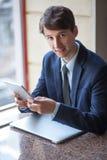 Το ένα χαλάρωσε τη νέα όμορφη επαγγελματική εργασία επιχειρηματιών με το lap-top, το τηλέφωνο και την ταμπλέτα του σε έναν θορυβώ Στοκ εικόνες με δικαίωμα ελεύθερης χρήσης
