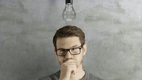Το έξυπνο δημιουργικό άτομο σκέφτεται ότι παίρνει μια ιδέα, η οποία ανάβει επάνω έναν συμβολικό λαμπτήρα πέρα από το κεφάλι του σ απόθεμα βίντεο