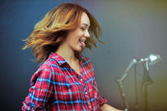 Το έξυπνο κορίτσι διασκέδασης στο ελεγμένο πουκάμισο παρουσιάζει γλώσσα Στοκ Φωτογραφία