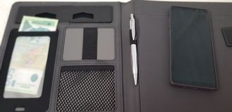 Το έξυπνο τηλέφωνο βάζει στον ανοικτό φάκελλο δέρματος με μια μάνδρα και σερβικά χρήματα εγγράφου στοκ φωτογραφία με δικαίωμα ελεύθερης χρήσης
