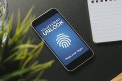Το έξυπνο τηλέφωνο με το δακτυλικό αποτύπωμα ξεκλειδώνει το σύστημα στην οθόνη, που τοποθετείται σε έναν μαύρο πίνακα Στοκ φωτογραφία με δικαίωμα ελεύθερης χρήσης