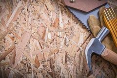Το δέρμα ασφάλειας φορά γάντια στο ξύλινο σφυρί νυχιών μετρητών handsaw σε OSB Στοκ Εικόνα