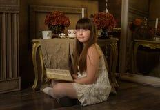 Το έφηβη διαβάζει ένα βιβλίο σε ένα δωμάτιο Στοκ Φωτογραφία