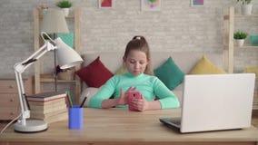 Το έφηβη με μια του προσώπου ατέλεια χρησιμοποιεί μια συνεδρίαση smartphone στον πίνακα στο σπίτι απόθεμα βίντεο
