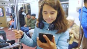 Το έφηβη με το smartphone και τα ακουστικά μέσα σε ένα αυτοκίνητο υπογείων πολλοί άνθρωποι συσσωρεύουν τον υπόγειο υπόγειο μετρό απόθεμα βίντεο