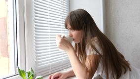 Το έφηβη πίνει το τσάι στη στρωματοειδή φλέβα παραθύρων κοντά στο παράθυρο Όμορφο λυπημένο κορίτσι που φαίνεται έξω το τσάι ή ο κ φιλμ μικρού μήκους