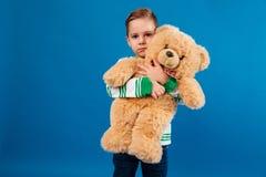 Το ήρεμο νέο αγκάλιασμα αγοριών teddy αντέχουν και η εξέταση τη κάμερα Στοκ Φωτογραφίες