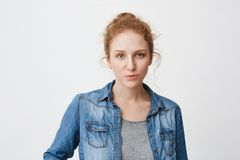 Το ήρεμο σοβαρό καυκάσιο κορίτσι πιπεροριζών με την τρίχα κτένισε στο κουλούρι, εκφράζοντας την ενόχληση ή την αδιαφορία στεμένος στοκ εικόνα με δικαίωμα ελεύθερης χρήσης